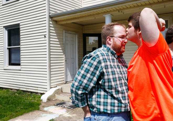 Mark Butler, left, gets a kiss from his son, Andrew, in front of the Ironton apartment where Andrew lived in 2016. Mark Butler and his wife, who live more than two hours away in Whitehall, had to relinquish custody of Andrew when he was 16 for him to access the behavioral health services he needed. (Columbus Dispatch photo by Fred Squillante)