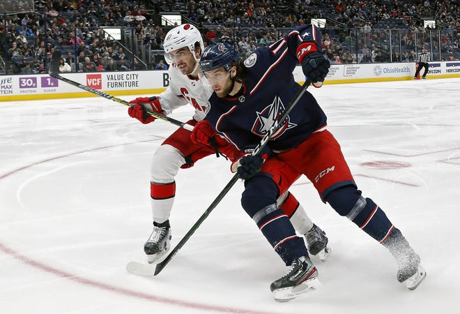 Blue Jackets center Kevin Stenlund (11), shown chasing after a puck against Carolina Hurricanes defenseman Trevor van Riemsdyk (57), accepted a one-year, two-way qualifying offer Wednesday to remain with the team for the 2020-21 season. Stenlund signed after forward Calvin Thurkauf accepted a similar deal Tuesday.