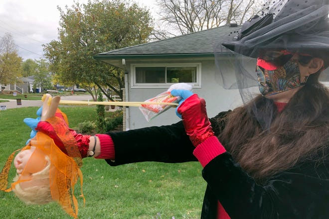 Julie Schirmer of Clintonville demonstrates the slingshot she originally planed to use to deliver Halloween candy from afar during the city's trick-or-treat night on Thursday.