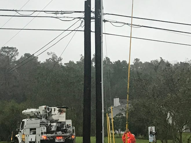 An Entergy worker handles a power outage this evening in Chackbay as wind and rain arrive from Hurricane Zeta.