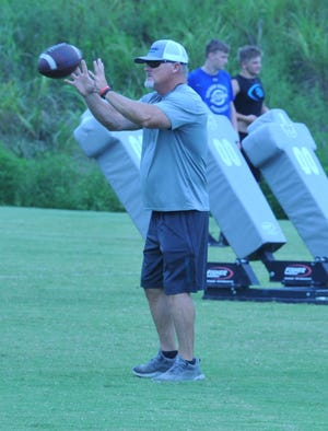 Oak Grove assistant coach Mike Meadows works with his players during a football workout in August.