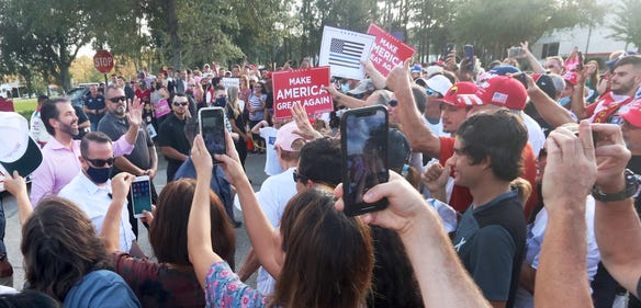 Donald Trump Jr., at left, waves to a large crowd Wednesday, October 28, 2020 during a campaign stop for his father, President Donald Trump, at Volusia Top Gun in Daytona Beach.
