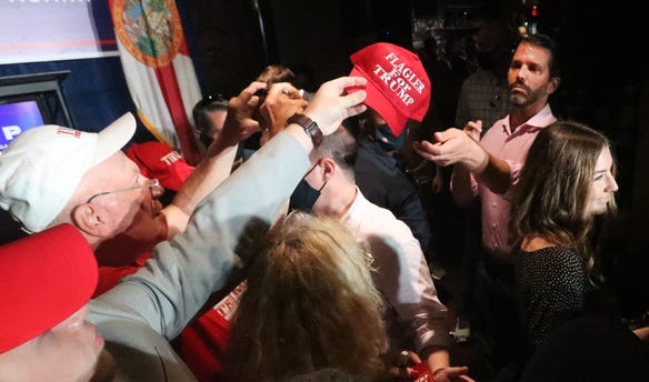 Donald Trump Jr. reaches for a hat to sign Wednesday, October 28, 2020 during a campaign stop for his father, President Donald Trump, at Volusia Top Gun in Daytona Beach.