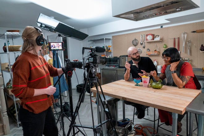 "Producer Jessica Opon, left, films Andrew Rea, founder of the Binging with Babish network, center, as he tastes popcorn ice cream created by chef Sohla El-Waylly, during a taping of the ""Stump Sohla,"" series in New York."