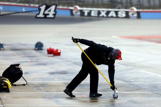 A member of Erik Jones' pit crew squeegees water out of the pit area as crews prepare to resume a NASCAR Cup Series race Tuesday at Texas Motor Speedway in Fort Worth, Texas. The race was stopped Sunday because of drizzle and misty conditions that allowed drivers to complete just 52 of 334 scheduled laps. Another 115 laps have to be completed to get to the halfway mark of 167 laps that would make Texas an official race.