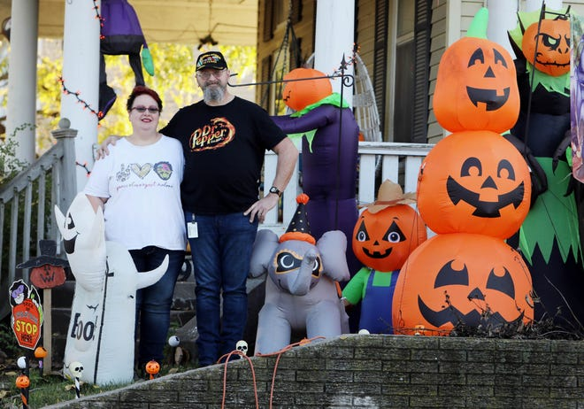 Mindy and Arron Doane stand amid some of their Halloween-themed inflatables Oct. 22 outside their North Hill home. Come Christmastime, the couple expects to have more than 50 inflatables and other decorations spreading holiday cheer to the neighborhood.