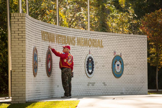 A U.S. Marine Corps veteran fixes an American flag above the Marine Corps seal at the Vietnam Veterans Memorial in Jacksonville before the start of the 32nd Beirut Memorial Observance Ceremony on Oct. 23, 2015.