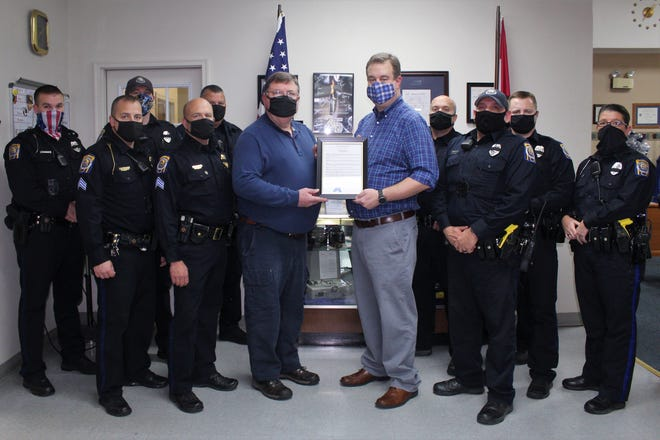 Kirksville Mayor Zac Burden, middle right, delivers the Steve Farnsworth Day proclamation to Police Lieutenant Mark Wellman and officers of the Kirksville Police Department.