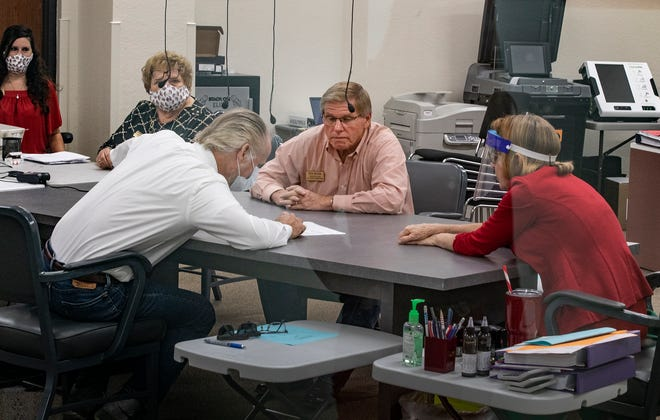 The Canvassing Board, which includes, from right, Supervisor of Elections Lori Edwards, County Commissioner Rick Wilson and Judge Robert Fegers, meets to review ballots at the Supervisor of Elections Office in Winter Haven on Wednesday. The board is meeting daily to analyze mailed in ballots.