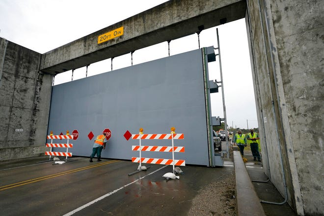Workers close a floodwall gate on Hwy 39 in Poydras, La., Wednesday, Oct. 28, 2020. Hurricane Zeta is expected to make landfall this afternoon as a category 2 storm.