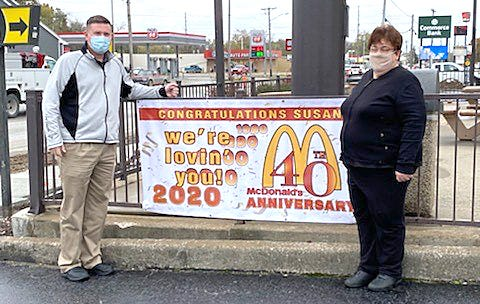 McDonald's of Moberly General Manager Susan Foster, right,  was recognized for her 40 years of service Tuesday during a surprise celebration held in her honor. Chuck Marshall, owner/operator of McDonald's of Moberly, is shown with Foster next to a banner erected at the restaurant.