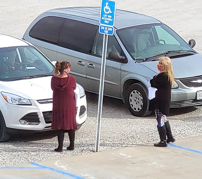 A bipartisan couple of election officials stand curbside at the Randolph County Justice Center in Huntsville accepting absentee ballots from a registered voter in advance of the Nov. 3 General Election.  (Courtesy of Randolph County Clerk's office)