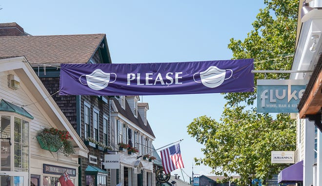 A sign in downtown Newport over Labor Day weekend reminds people to wear masks.