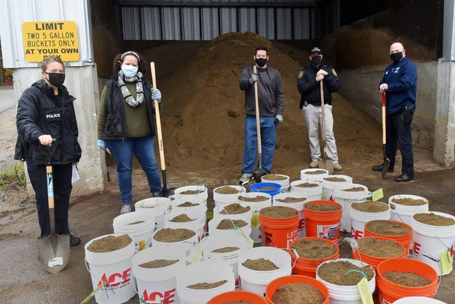 A group of volunteers gathered at the York Highway Department Wednesday to fill sand buckets and then delivered them to area seniors. The sand is used to keep stairs and walkways safe during winter months. From left is YPD Detective Jamie Robie, Attorney Britton Garon, Jon Gay of York Village Fire and Police, and York police officers Dave McKinnon and Shawn Darrow.