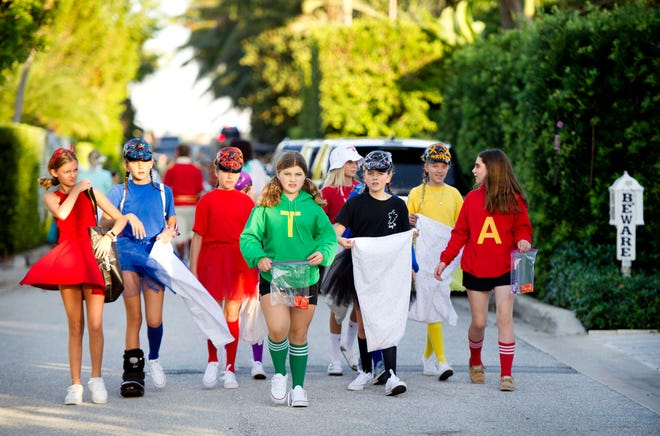 Hundreds of families in costumes walk Queen's Lane during Halloween trick-or-treating on the north end of Palm Beach last year. Many families are forgoing trick-or-treating this year amid the novel coronavirus pandemic.