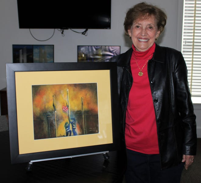 Artist Allie Lull stands by the first print of the 'Patriotic Rescue' painting she created after viewing the viral video of Hopewell Fire & Rescue firefighters rescuing the American flag and battling the fire that destroyed the Hopewell Moose Family Center on Feb. 28, 2019. Lull delivered her artwork to the Hopewell Visitor Center to donate to the Moose Lodge 1472 on Oct. 26, 2020.