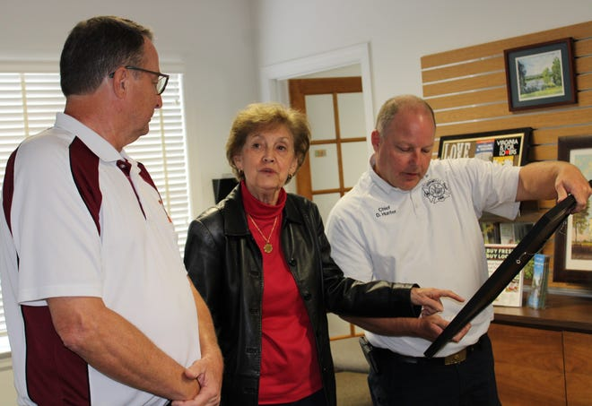 Artist Allie Lull describes the 'Patriotic Rescue' painting she created to, from left to right, Hopewell Moose Family Center Governor Joey McCaffrey and Hopewell Fire & Rescue Chief Donny Hunter at the Chamber/Hopewell Visitor Center on Oct. 26, 2020.