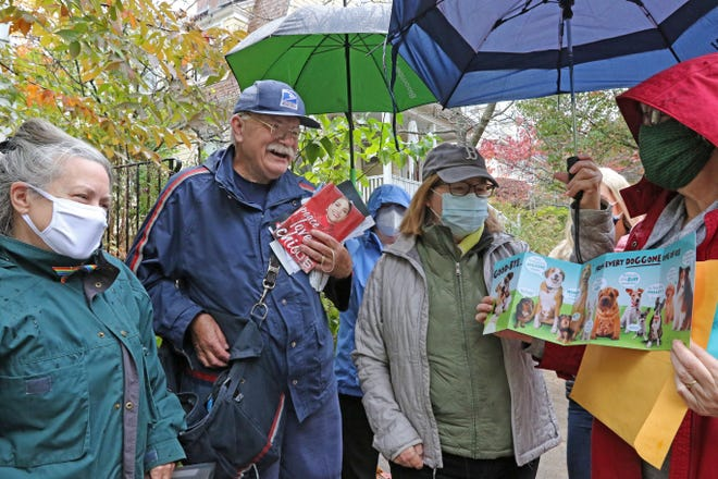 Sarah Morenon presents Bill Prevatt a dog-themed card that many of the neighbors had signed. At left is Rebecca Leuchak and at center is Lili Gilbert. Neighbors on the postal route of Bill Prevatt, mail carrier for more than 33 years, honored him Wednesday with thanks, cards, poems, and a proclamation from Providence Mayor Jorge Elorza.  [The Providence Journal / Sandor Bodo]