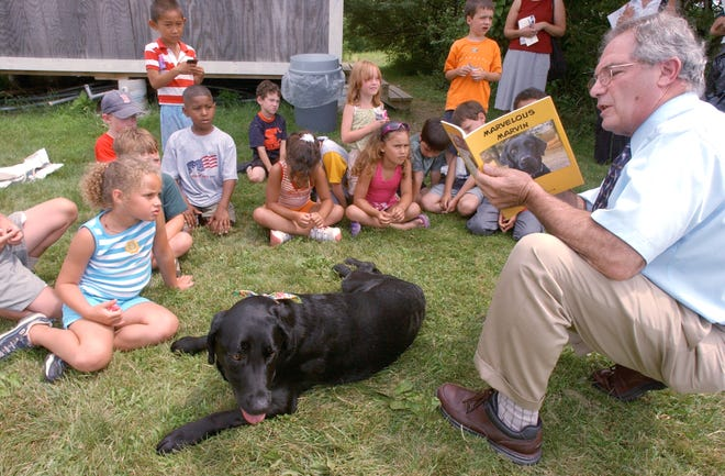 Marvelous Marvin, an adopted dog from the RISPCA, sits in front of a group of children at the South County YMCA as Dr. Finocchio reads the book he wrote about Marvin's life. [The Providence Journal, file / Bob Breidenbach]
