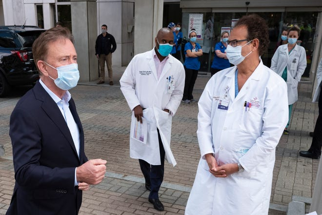 Connecticut Gov. Ned Lamont, left, talks with medical staff outside Saint Francis Hospital in Hartford in May. Connecticut this week lifted its quarantine order on travelers from Rhode Island. [AP, file / Mark Lennihan]