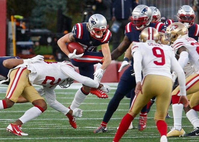 Patriots Gunner Olszewski hurdles over defenders on a first-half kickoff return on Sunday.