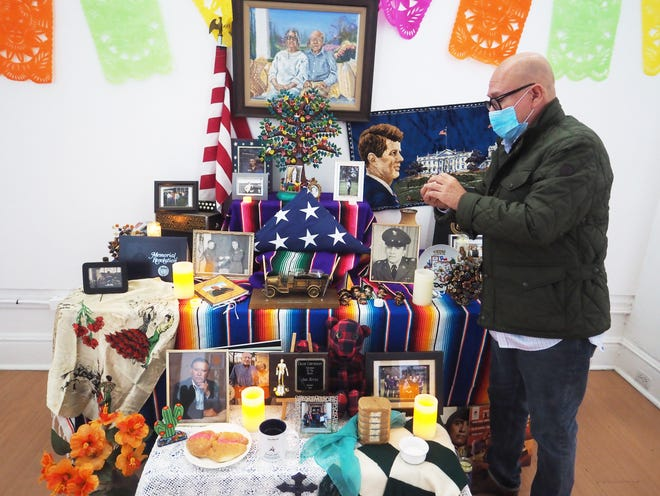 Joel Reyna Jr. stands near a picture of his father, Joel Reyna, in 2015 at an altar at the Mexican Heritage Center. Reyna will be featured at the annual Dia de los Muertos community street fiesta and family altars, which this year will be moving online and indoors amid the pandemic.