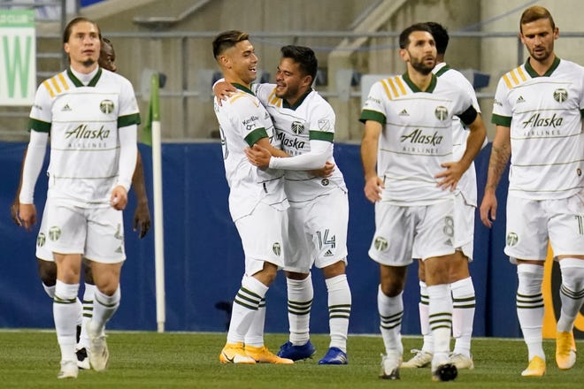 Portland's Andres Flores (14) is congratulated after scoring against the Seattle Sounders in the first half of an Oct. 22 MLS match in Seattle.