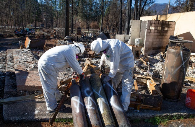 Crews from the Environmental Protection Agency work to clean up hazardous materials from burned buildings in Blue River, nearly two months after the Holiday Farm Fire swept through the area, destroying much of the rural town along the McKenzie River.