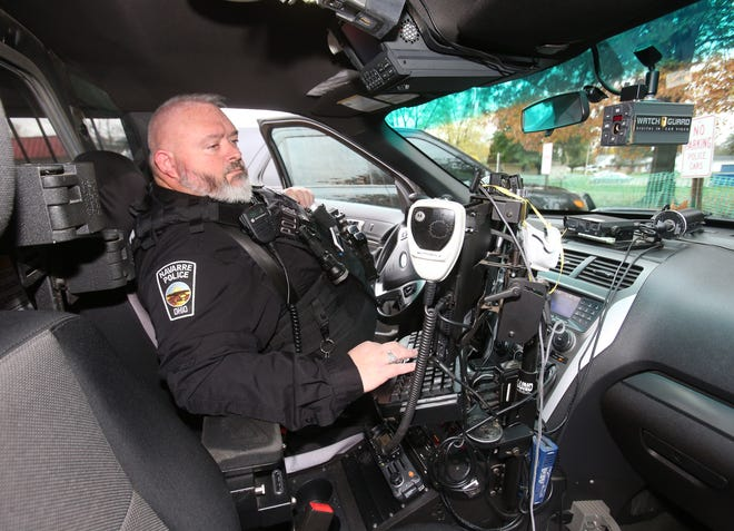 Detective Dan Kirby of the Navarre Police Department works inside his cruiser on Wednesday. Officers are seeking a pay raise to recruit and retain officers.