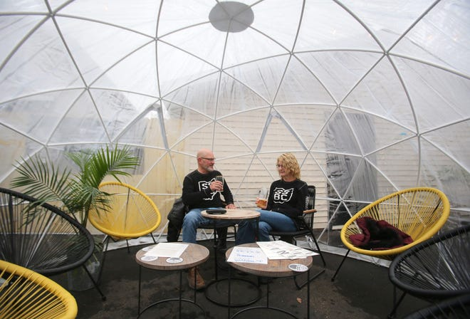 Gary and Pam Chambers enjoy an igloo on a new patio behind Sandy Springs Brewing Co. in Minerva. Local restaurants are trying to extend outdoor dining/drinking into the fall and winter.