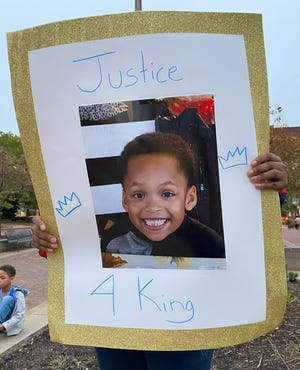 A protester holds a sign last month with the photo of 6-year-old King Pleasant. The Canton boy was fatally shot by an 11-year-old boy in Canton last month, according to police.