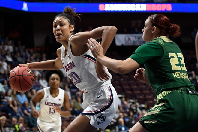 FILE - Connecticut's Olivia Nelson-Ododa, left, drives around South Florida's Tamara Henshaw during last season's American Athletic Conference tournament at Mohegan Sun Arena.
