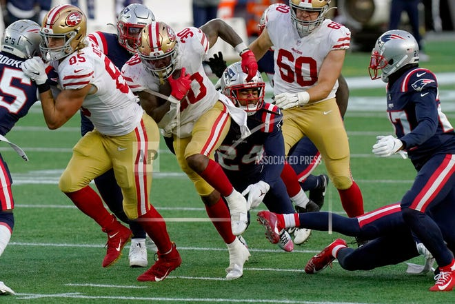 San Francisco 49ers running back Jeff Wilson Jr. (30) runs from New England Patriots cornerback Stephon Gilmore (24) last Sunday in Foxborough, Mass.