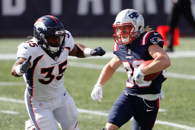 The Patriots' Gunner Olszewski, right, runs past Broncos special teamer Jeremy Cox during the second quarter on Oct. 18.