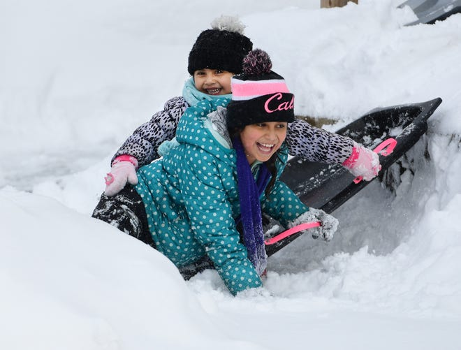 Elaina Moran-Herrera, 9, and her sister Analia, 5, slide on a snowbank along Perry Avenue in Worcester on a snow day last December.
