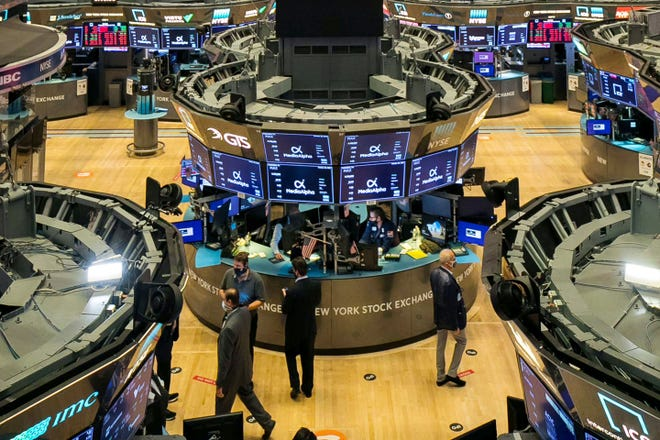 In this photo provided by the New York Stock Exchange, traders work on the floor during the MediaAlpha IPO Wednesday.