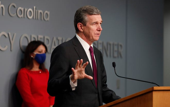 Gov. Roy Cooper said he could reimpose restrictions if the state can't stop the growth in new coronavirus cases North Carolina has seen in recent weeks. [AP FILE PHOTO]
