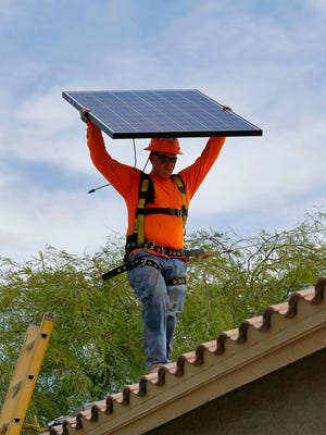 An electrician installs a solar panel on the roof of a home.