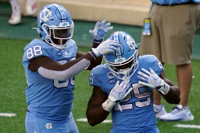 North Carolina tight end Kamari Morales, left, congratulates running back Javonte Williams after a touchdown during last week's defeat of N.C. State.