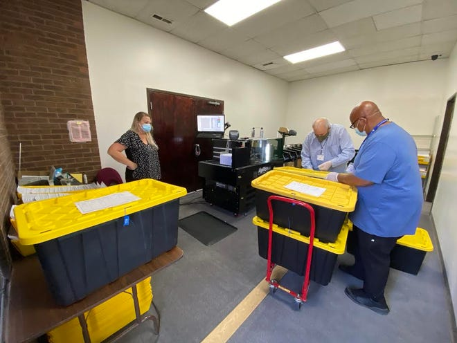 Pueblo County  election judges load ballots at a polling center earlier this month. Voters can no longer mail in their ballots.
