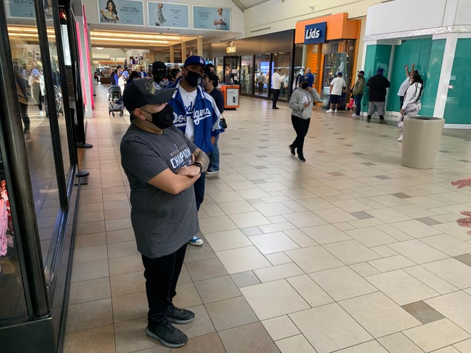 Hesperia resident Franky Bernal stands at the front of a line of Dodgers fans waiting to enter Fanzz inside the Mall of Victor Valley on Wednesday morning, Oct. 28, 2020.