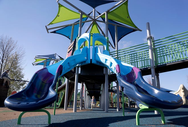 Bastian Young, center, walks under play equipment at the Universal Playground at Memorial Park in Appleton.