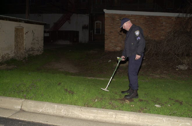 Former Battle Creek Police Department Sgt. Martin Brown uses a metal detector to search for evidence after the 2006 shooting that killed Benjamin Holmes.