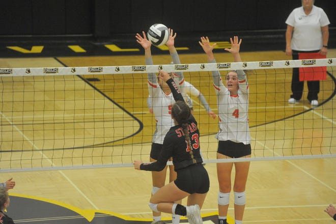 Buckeye Central's Kennedy Phenicie (9) and Lauren Mann (4) try to block a ball at the net hit by St. Paul's Presley Stang.
