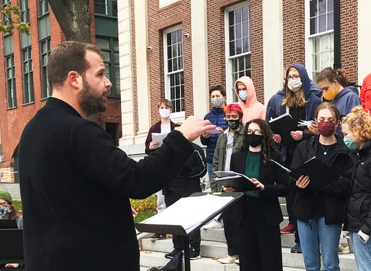 Billy Ray Poli conducts a choral rehearsal/performance by Burlington High School students on the western steps of City Hall on Oct. 28, 2020.