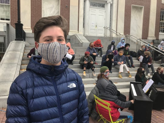 Daniel Gibson, a sophomore at Burlington High School, dons a mask before joining a rehearsal of the school's choir on the western steps of Burlington City Hall on Oct. 28, 2020.