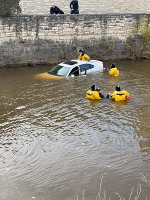 A Fond du Lac Fire and Rescue team rescues two people after a car plunged into the Fond du Lac River Wednesday afternoon.