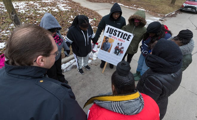 Family and friends of Otis Jones Jr. pray earlier this year before marching in the area where he was shot and killed. The case was ruled self-defense, but his family is still seeking answers.