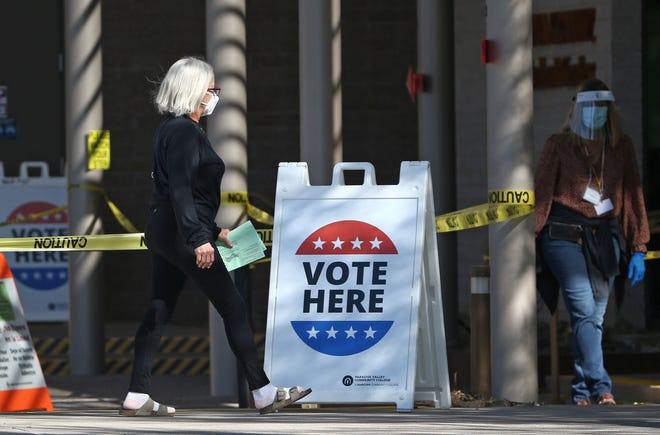 A voter takes her ballot to an early voting site at Paradise Valley Community College in Phoenix on Oct 28, 2020.