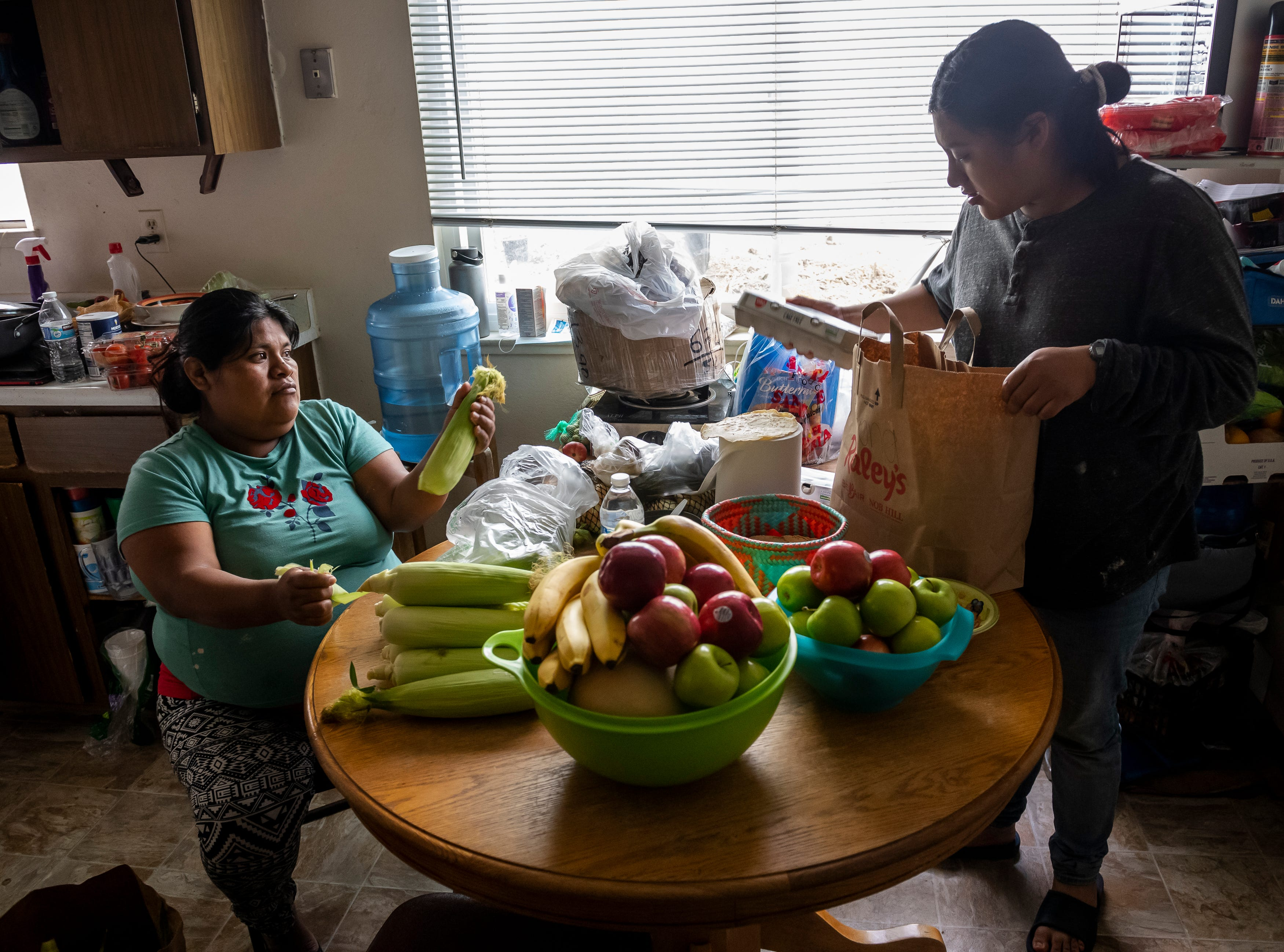 Constanza Aguilar, 35, shucks corn as she helps her stepdaughter, Resi Salvador, empty out all the bags of donated groceries inside the two-bedroom apartment that she rents with her family in north Salinas, Calif., on Saturday, July 18, 2020.